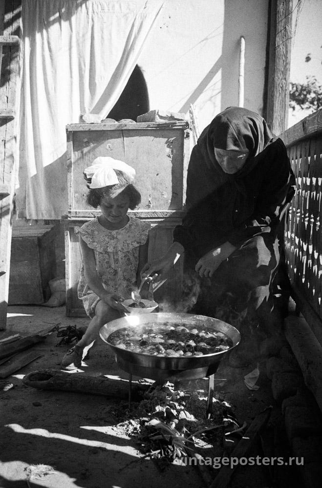Пожилая женщина с внучкой готовит еду на углях. Грузия. 1956г.