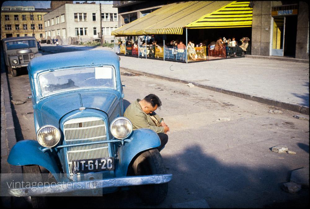 Мужчина уснул на подножке автомобиля напротив уличного кафе. Варшава, Польша. 1956г.