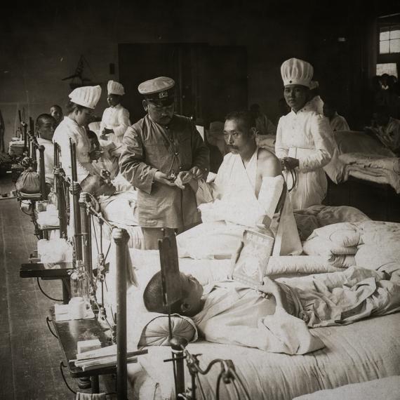 Доктор считает пульс у японского военнослужащего получившего ранения в ходе боевых действий во время Русско-Японской войны