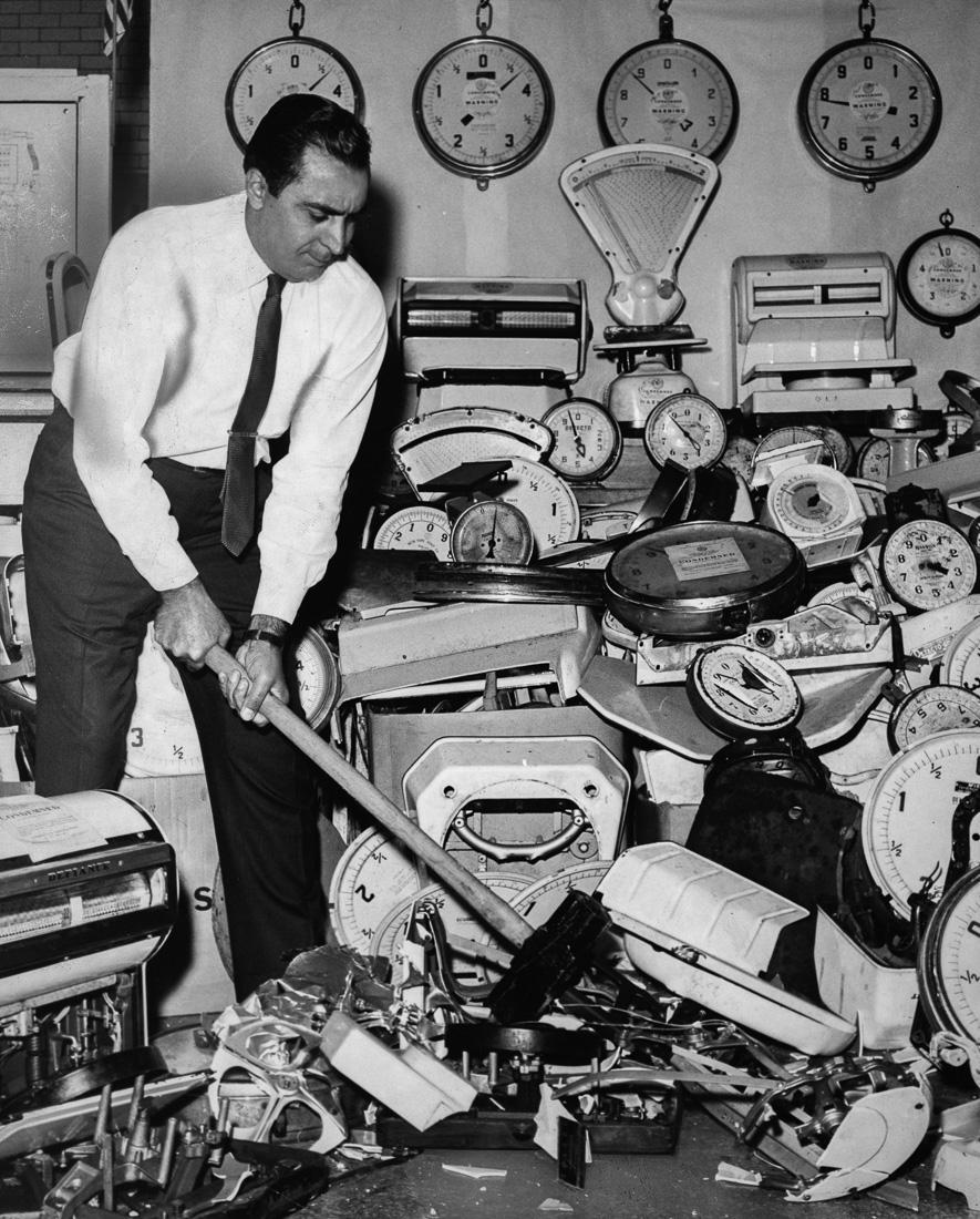 Комиссар по рынкам Нью-Йорка разбивает кувалдой конфискованные весы, 1964 год.