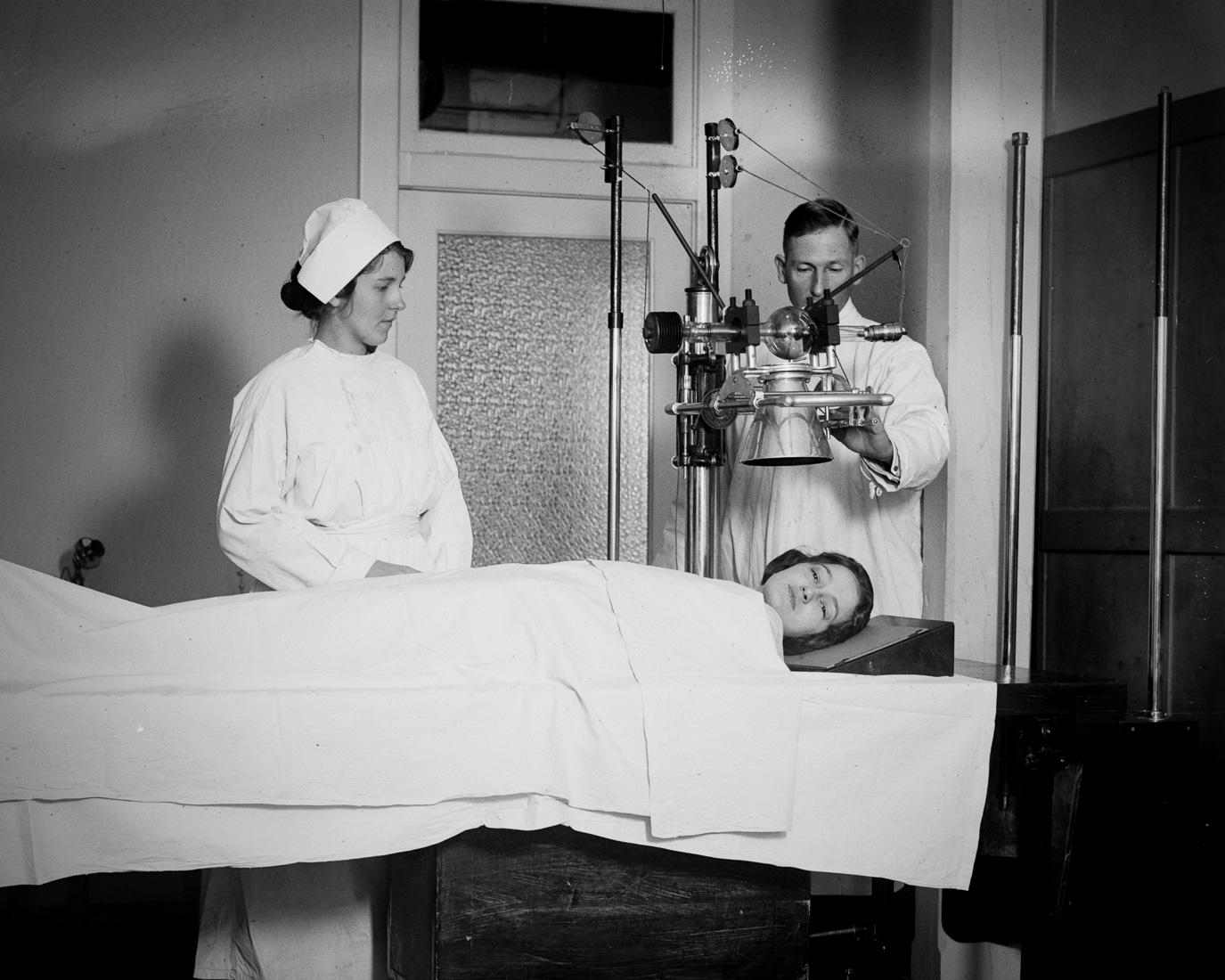 Персонал больницы делает рентгеновский снимок головы пациента, США, 1920 год.